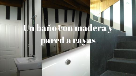 Un baño con madera y pared a rayas